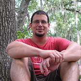 Portrait of Gerardo Celis sitting with trees in the background.