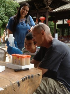 Researcher Paul Dijkstra in China showing child water sample from hot springs.