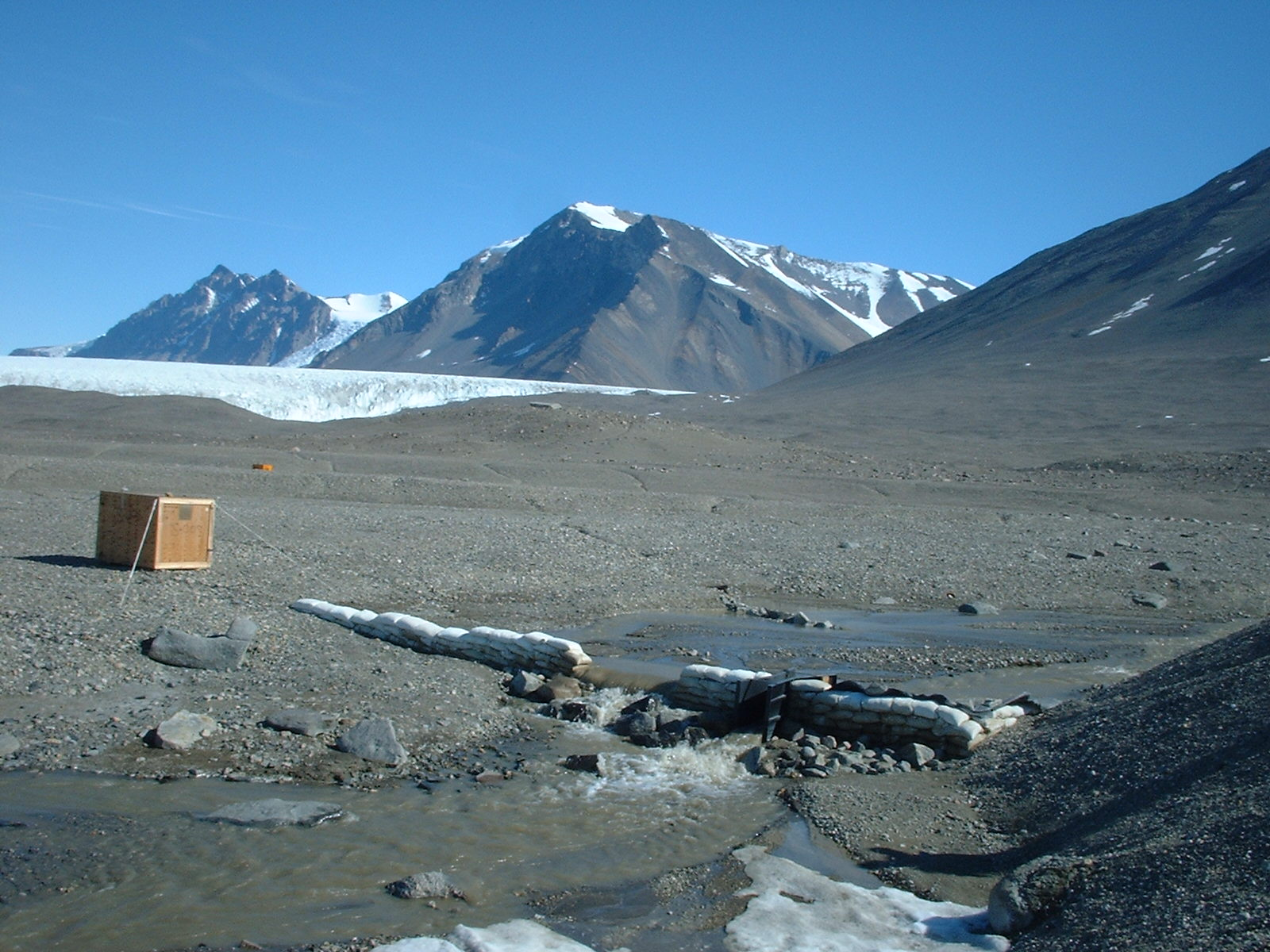 Field site in Antarctica with a crate in the foreground and steep mountains in background.