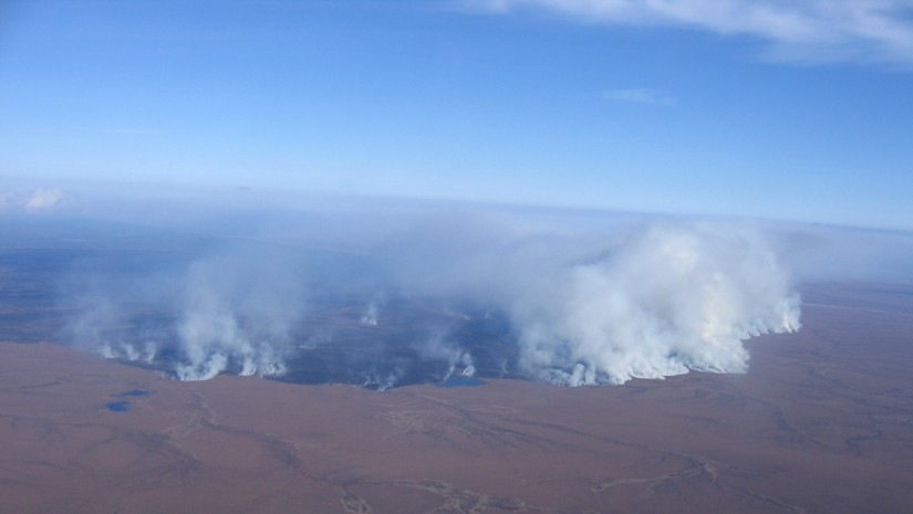 View from an airplane of the smoke and blackened land in the Anaktuvuk River area in Alaska due to a wildfire.