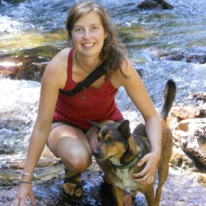 Portrait of Rebecca Fritz at a creek with a dog.