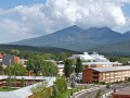 Northern Arizona University campus in the summer showing buildings in the foreground and the San Francisco Peaks in background.