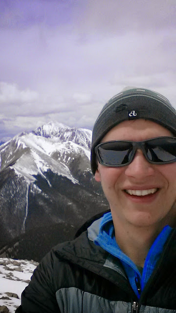Portrait of graduate student Brian Howard with snow-covered mountains in the background.