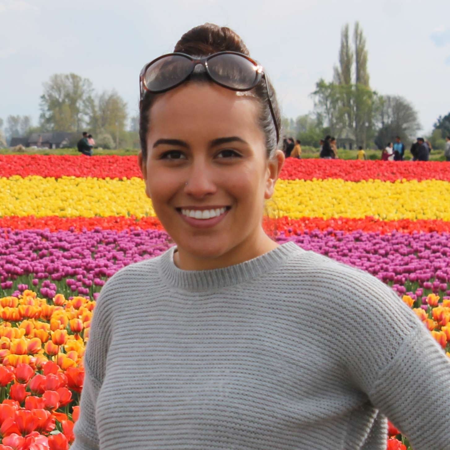 Photo of Alee Zuniga standing in a field of colorful tulips.