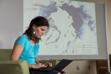 Researcher Christina Schaedel works on a laptop before a map of the Arctic