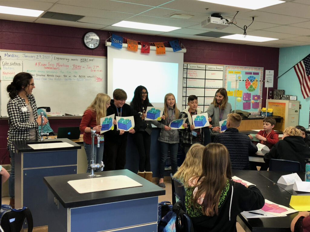 PhD Candidate Ayla Martinez leads a classroom exercise with her students. Six students stand in front of the classroom with colored illustrations of an ecosystem as other students sit and listen.